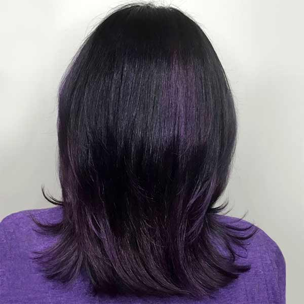 dark hairstyle on woman with purple accent highlights